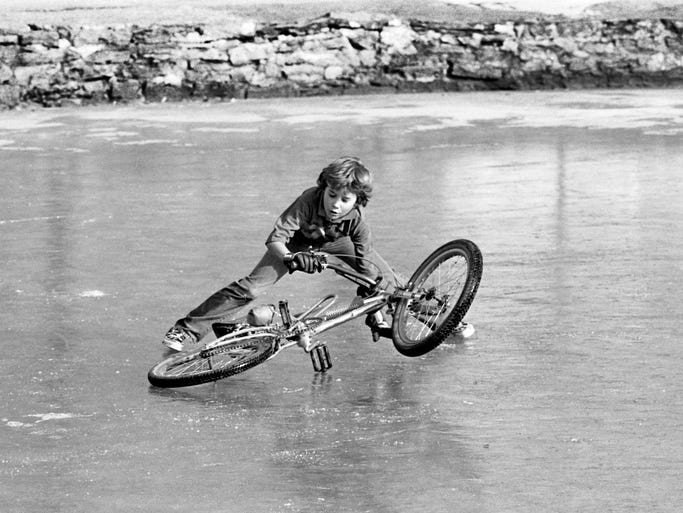 Shane Johnson, 11, of Acklen Park Drive has a hard time getting on his bicycle after a spill on a frozen Lake Watauga in Centennial Park Jan. 1, 1984.