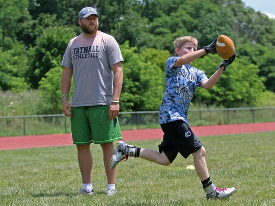 Green Bay Packers tight end Justin Perillo, a Tatnall School graduate, watches 11 year-old Justin Hahn catch the ball during a drill at Tatnall football camp on Thursday.