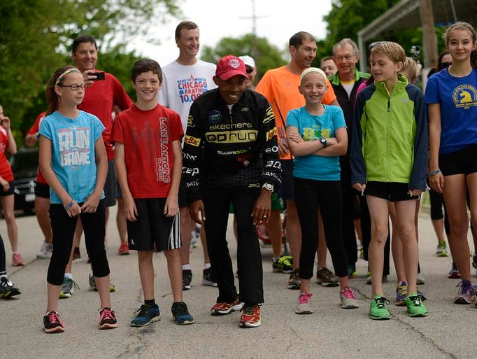 In middle, Boston Marathon winner Meb Keflezighi is all smiles as he lines up next to Blake Maxwell at the starting line during the Bellin Run Charity Fun Run with Meb in Green Bay on Friday, June 13, 2014.