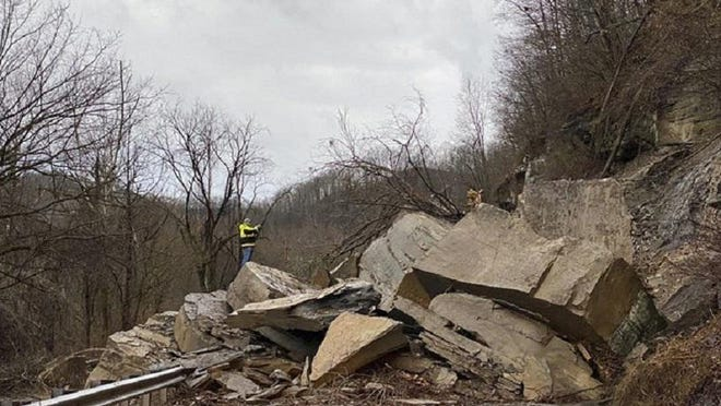 Workers assesses a rock slide along old U.S. Route 52 in Williamson, W.Va.