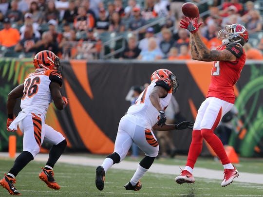 Tampa Bay Buccaneers wide receiver Mike Evans (13) comes down with a catch as Cincinnati Bengals cornerback Darqueze Dennard (21) and Cincinnati Bengals strong safety Shawn Williams (36) defend in the first quarter during the Week 1 NFL preseason game between the Tampa Bay Buccaneers and the Cincinnati Bengals, Friday, Aug. 11, 2017, at Paul Brown Stadium in Cincinnati.
