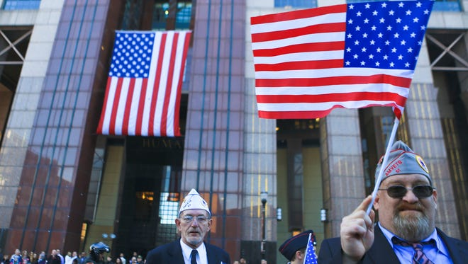AMVETS Post 61 member Danny Davis waves a flag during the Veterans Day parade on Main Street Wednesday in Louisville.