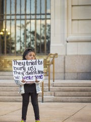 A young Black Lives Matter group member holds a sign as Aziza Love perfroms a song in front of the Hamilton County Courthouse Saturday, October 22, 2016, before the start of the Tensing trial on Tuesday. The former Univeristy of Cincinnati police officer Ray Tensing is charged with murder in the shooting death of Sam DuBose.