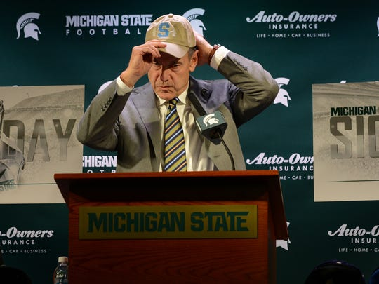 Michigan State football head coach Mark Dantonio puts on a hat during his Signing Day press conference Wednesday, Feb. 1, 2017 at Spartan Stadium. Dantonio wore various hats to represent the new players.