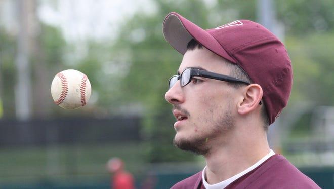 Western Hills senior David Offenbacker flips a baseball to himself between innings against Hughes on May 3, 2017.