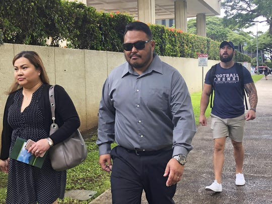 Former Honolulu police officer Reginald Ramones, center, walks down a street in Honolulu. As part of a deal with prosecutors, Ramones in September pleaded guilty to a lesser charge that he knew fellow officer John Rabago committed a civil rights violation but didn't inform authorities about it. Rabago is expected to plead guilty to depriving a homeless man of his civil rights by forcing him to lick a public urinal.