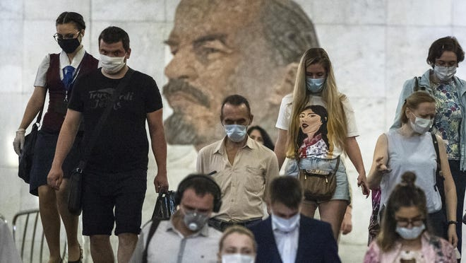 People wearing face masks to protect against coronavirus walk through the subway, with a portrait of Soviet founder Vladimir Lenin in the background, in Moscow, Russia, Wednesday, June 10, 2020. Moscow residents are no longer required to stay at home or obtain electronic passes for traveling around the city. All restrictions on taking walks, using public transportation or driving have been lifted as well.