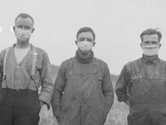 Farmers wear masks in the early 1900s to try to avoid catching the Spanish flu.