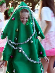 Jordyn Barrett, 6, of Littleton Elementary School leaves the stage in her Christmas tree costume after performing with Lariats and Lace during the Centurylink Holiday Festival of Lights in Cape Coral.