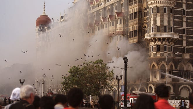 Locals look at a fire as it burns at Taj Mahal Palace & Tower Hotel following the armed siege in Mumbai on Nov. 29, 2008.