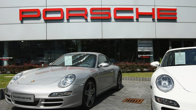 FILE - Sports cars of German automaker Porsche stand on display at a dealership.