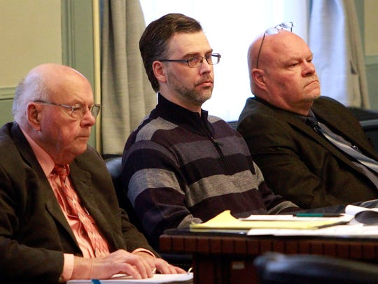 Shawn Grate sits with his attorneys Robert and Rolf