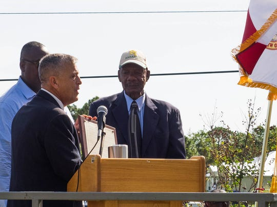 County Commission Chairman Joe Flescher reads from the proclamation dedicating Gifford Park as the Victor Hart Sr. Community Enhancement Complex at a ceremony on Oct. 21, while Hart looks on.