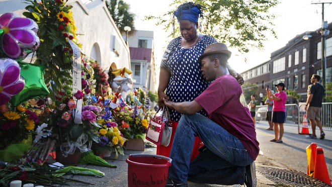 FILE- In this June 20, 2015, file photo, Allen Sanders, right, kneels next to his wife, Georgette, both of McClellanville, S.C., as they pray at a sidewalk memorial in memory of the shooting victims in front of Emanuel AME Church in Charleston, S.C. One big change happened in conservative South Carolina after a racist gunman killed nine black people during a Bible study five years ago -- the Confederate flag came down. But since then, hundreds of other monuments and buildings named for Civil War figures, virulent racists and even a gynecologist who did painful, disfiguring medical experiments on African American women remain.