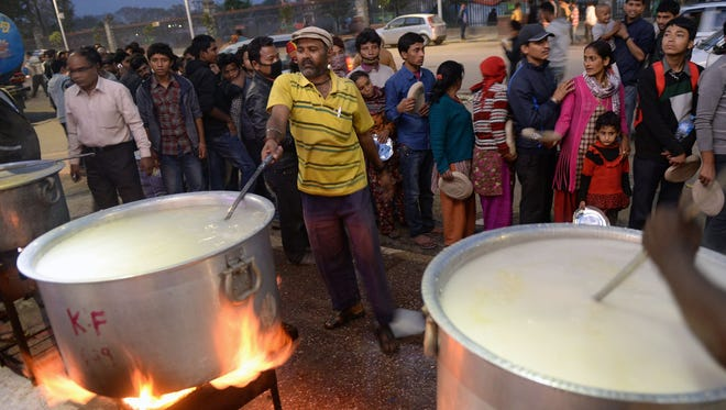 """Nepalese people stand in line to get food from a community kitchen in Kathmandu on April 27, 2015. Nepalis started fleeing their devastated capital on April 27 after an earthquake killed more than 3,800 people and toppled entire streets, as the United Nations prepared a """"massive"""" aid operation.  AFP PHOTO/PRAKASH SINGHPRAKASH SINGH/AFP/Getty Images"""