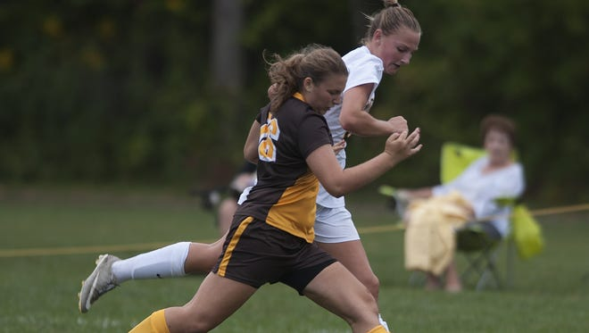 Moorestown's Anni Nisen, 20,  left, battles for the ball against Delran's Natalie Acker, during the first half of a 0-0 draw.