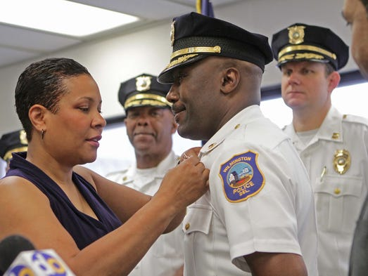 Simone Cummings pins her husband, Bobby Cummings, with his new chief of police badge for the City of Wilmington during a ceremony at the mayor's office on Friday, May 30, 2014.