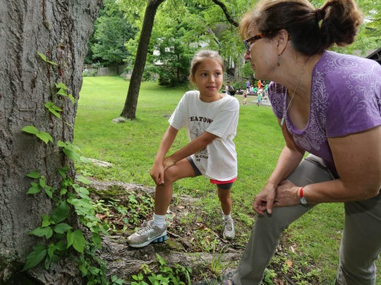 Camper Sara Farrell, 9 of Ossining, talks with Phyllis Bock, the Education Director at Teatown Lake Reservation in Ossining as they look over as a tree with poison ivy at the base, July 10, 2015.