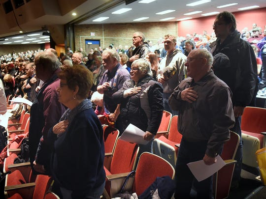 Audience members say the Pledge of Allegiance during a 2016 political caucus at Apollo High School in St. Cloud.