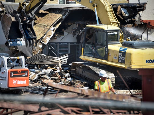 Crews work on demolishing the former Holiday station Thursday, July 6, on the East Side of St. Cloud.