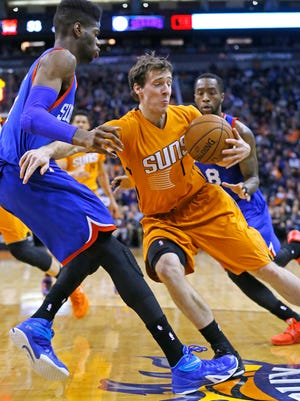 Phoenix Suns guard Goran Dragic (1) tries to spin away from Philadelphia 76ers forward Nerlens Noel (4) during the first half of their NBA game Friday, Jan. 2, 2015 in Phoenix, Ariz.