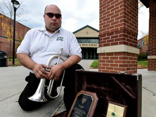 Owego resident Mark Dowches, former bandleader for the Vestal Marching Band, stands next to some of the plaques from his history from the band.