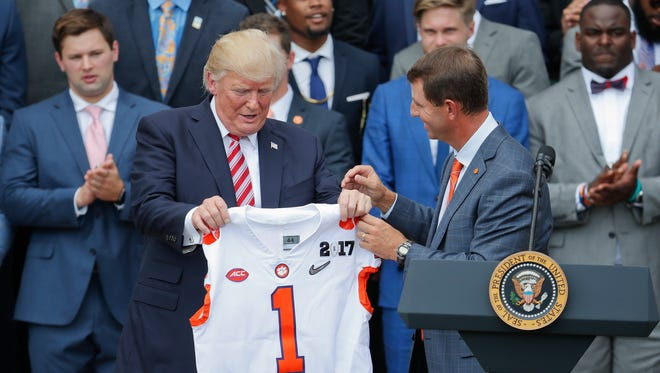Clemson coach Dabo Swinney presents President Trump with a jersey during the national champion Tigers' visit to the White House.