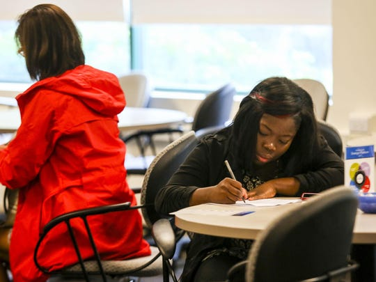 Shelda Romulus fills out paper work as she applies