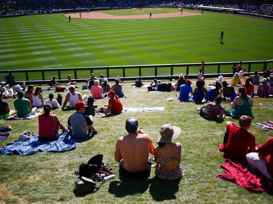 Baseball fans watch the game from the lawn as the Arizona