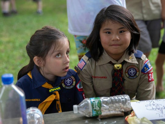 Lorelei Forman, 7, and Luci Juchniewicz, 10, listen to instructions as the Cub Scouts build their boats for Pack 34's Raingutter Regatta in Jackson.