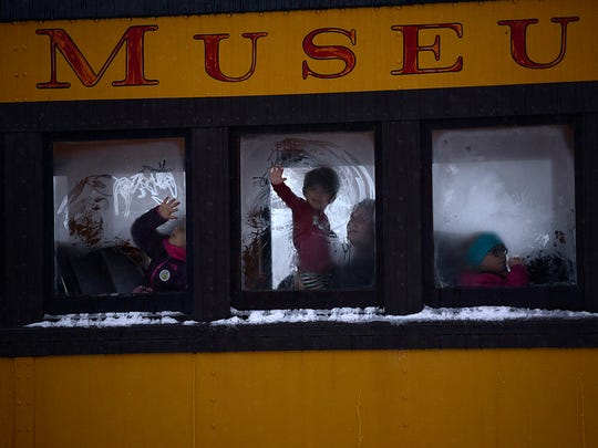 Children peer through the windows as they take a train ride during The Polar Express event at the National Railroad Museum in Ashwaubenon.