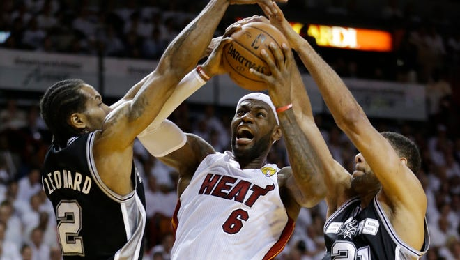 San Antonio Spurs forward Tim Duncan (21) and forward Kawhi Leonard (2) defend Miami Heat forward LeBron James (6), during the first half in Game 3 of the NBA basketball finals, June 10, 2014, in Miami.