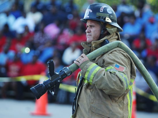 A Tallahassee firefighter stands by during a bus crash exercise. Workers from various city and county emergency services swarmed a bus Monday that was toppled on its side for an exercise in crash response. School officials and others watched the drill.