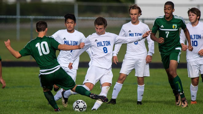 Milton's Cameron Goodrich, center, and Enosburg's Parker Snow, left, close in on the ball in Milton on Wednesday, September 14, 2016.