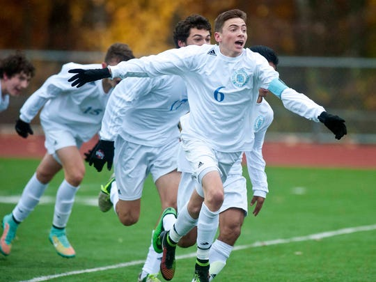 South Burlington's Alex Pasanen celebrates after scoring the equalizer with 8.4 seconds left in regulation against Essex to send the match into overtime during the Boys' Division 1 state championship in Burlington in November.