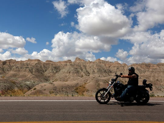 A lone biker drives the Badlands Loop in Badlands National