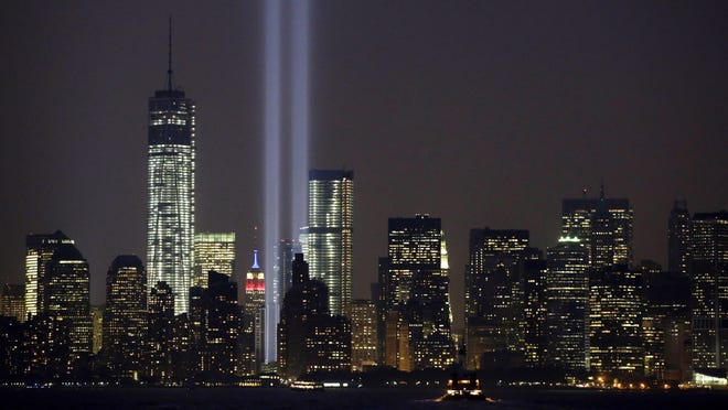 FILE - In this Wednesday, Sept. 11, 2013, file photo, the twin beams of the annual Tribute in Light commemorating the Sept. 11, 2001, terrorist attacks shine amid the city's skyline, in New York. The twin beams of light representing the World Trade Center towers won't be beamed into the sky during the 2020 memorial of the 9/11 terror attacks in New York City, because of concerns about the coronavirus and the health of work crews.