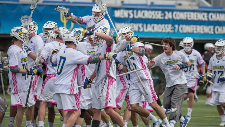 Delaware players celebrate after beating top-ranked Rutgers 13-9 in men's lacrosse.