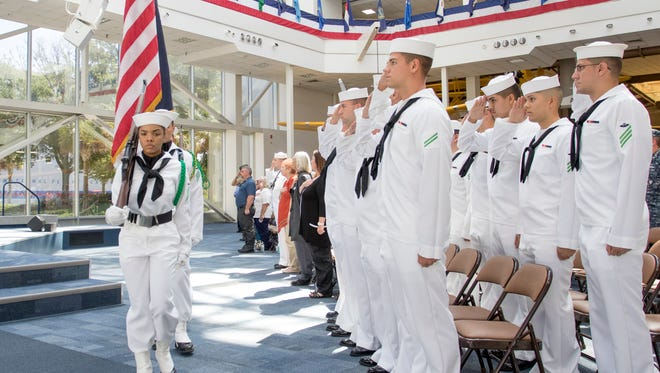 Sailors salute as the color guard marches past during the Gold Star Remembrance ceremony at the National Museum of Naal Aviation at Naval Air Station Pensacola on Thursday, September 22, 2016.