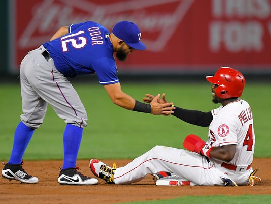 Texas Rangers second baseman Rougned Odor, left, helps Los Angeles Angels' Brandon Phillips up after Phillips was forced out at second on a ball hit by Mike Trout during the first inning of a baseball game, Friday, Sept. 15, 2017, in Anaheim, Calif. (AP Photo/Mark J. Terrill)