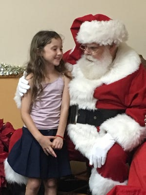 Santa pays a visit to children during the December meeting of the St. Lucie County Foster Parent Association.