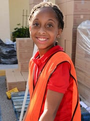 S'Nahra Wallace Wilson, the youngest volunteer, prepares