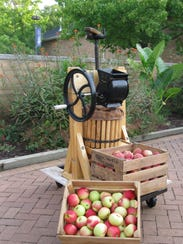 This small, hand-operated apple grinder and press can