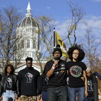 Graduate student Jonathan Butler, center, addresses a crowd Nov. 9 following the announcement that University of Missouri System President Tim Wolfe would resign, in Columbia, Mo.