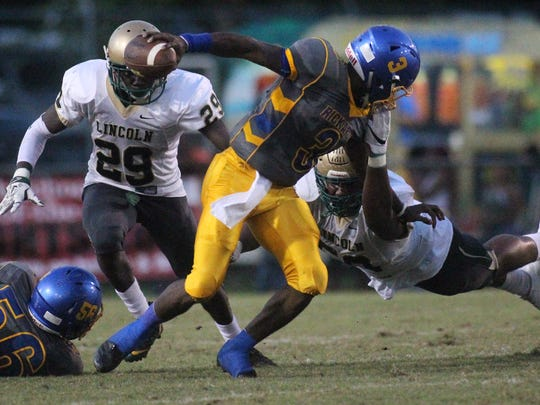 Rickards quarterback Marcus Riley is taken down by