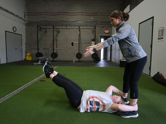 Exercise physiologist Missy Sachs, right, helps Katherine Phinney, 9, perform abdominal exercises during a prime class at the Louisville Youth Training Center.