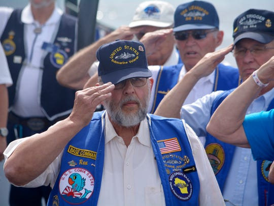 "Ron MacDonald, the base commander for the Wisconsin Submarine Veterans Base, salutes as the Capitol Civic Centre Community Chorale plays ""Taps"" on Sunday. MacDonald helped to lead the Tolling of the Boats Memorial Ceremony on the deck of the USS Cobia."