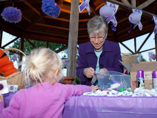 COPE Executive Director Kay Gomolak passes out bracelets honoring domestic violence survivors at their vigil last year. COPE is hosting a Dancing for the Causer event Feb. 16.
