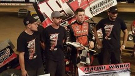 Brent Marks, third from left, and his crew savor a win in victory lane after taking the Fred Rahmer Promotions 410 Sprint race Sunday.