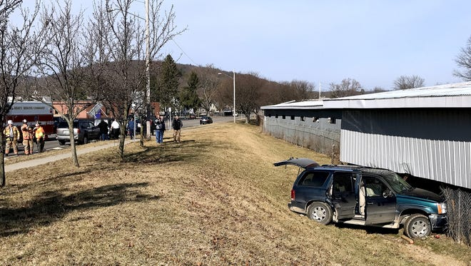 A Cadillac Escalade sits where it crashed Tuesday morning into the side of a Chapel Lumber building in the Town of Southport.